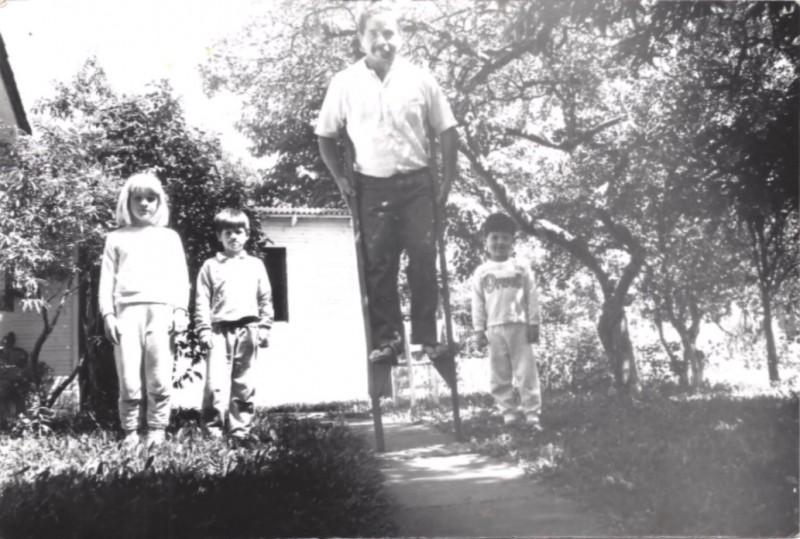 Foto onde aparece José em uma perna de pau, com três crianças à sua volta